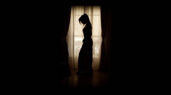 窓際に立つ女性のシルエット