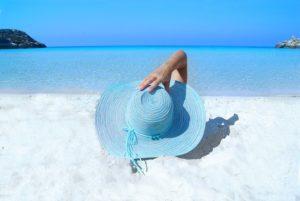 海辺でブルーの帽子をかぶる女性