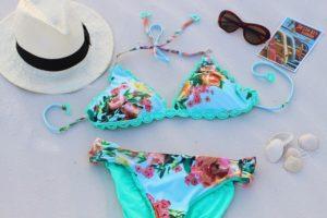 砂浜にある水着と帽子とサングラス
