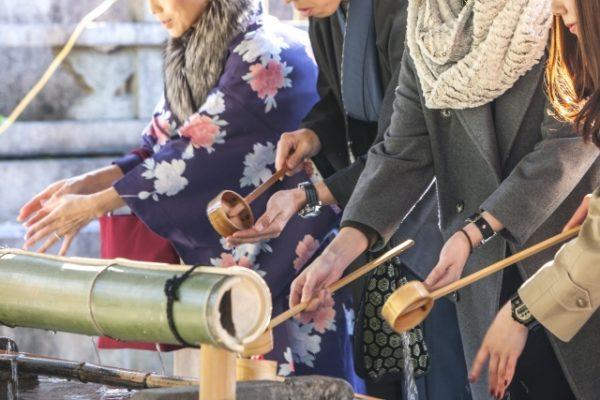 神社の手水を使う男女