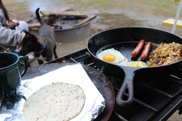 スキレットで調理される卵とウインナー