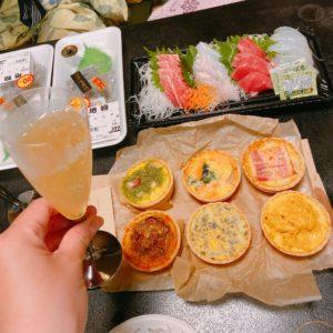 テーブルに広げられた料理とシャンパンを持つ手